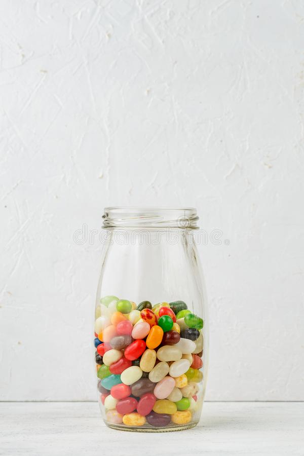 Pot en verre complètement de dragées à la gelée de sucre colorées photographie stock