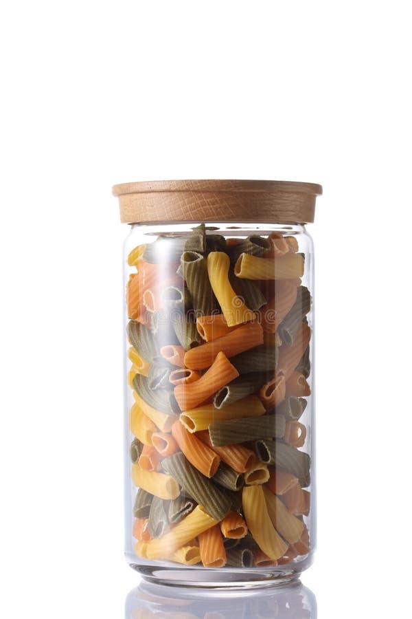 Pot en verre contenant les pâtes crues de trois couleurs d'isolement sur le fond blanc avec le chemin de coupure et l'espace de c photos stock