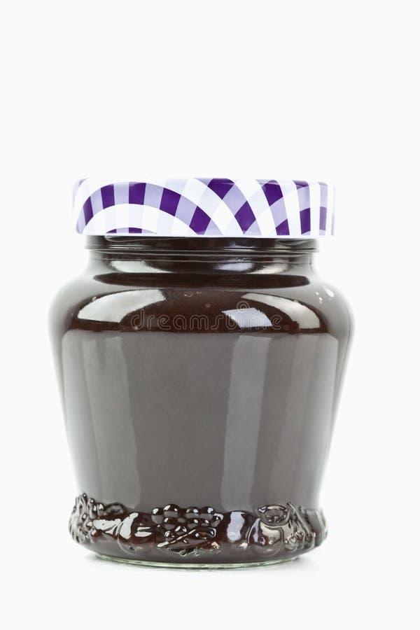 Pot en verre de confiture de prune sur le fond blanc photos stock