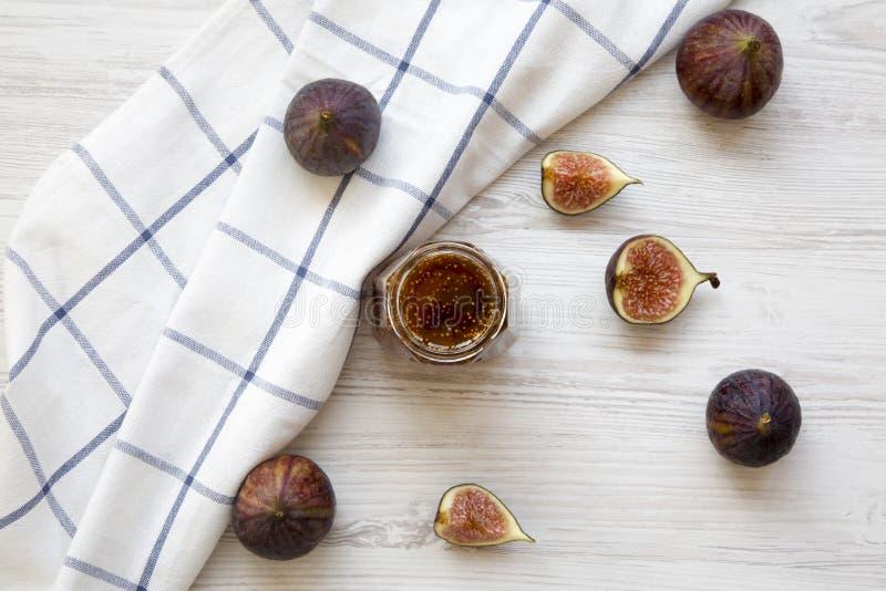 Pot en verre de confiture de figue et de figues fraîches sur le fond en bois blanc Vue supérieure photos libres de droits