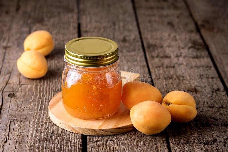 Pot en verre de confiture savoureuse faite maison d'abricot et d'abricots mûrs sur le fond en bois horizontal image libre de droits