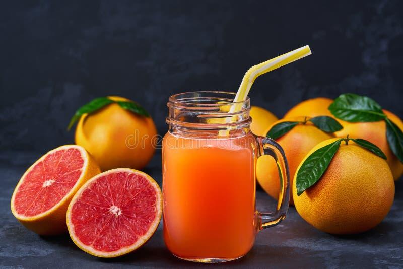 Pot en verre de jus de pamplemousse frais avec des fruits frais sur t foncé photographie stock