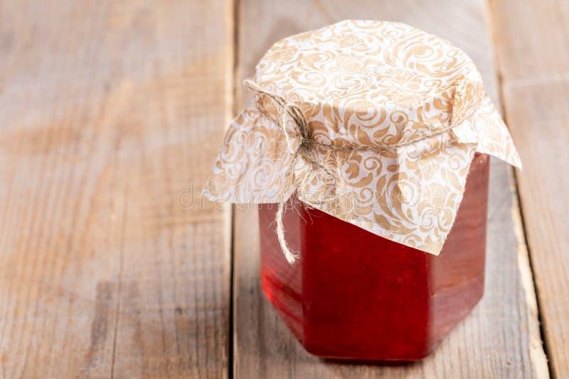 Pot en verre fermé de plan rapproché avec de la confiture de fraise faite maison sur la vieille table en bois photographie stock libre de droits