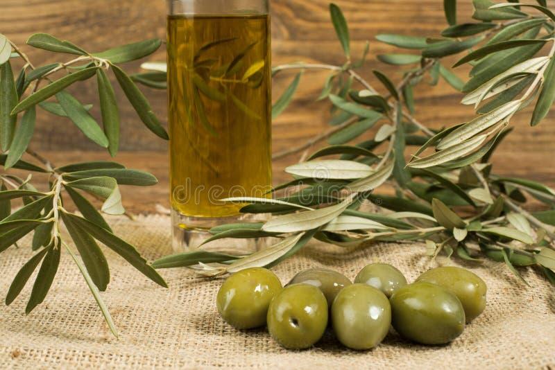 Pot et feuilles en verre d'huile d'olive de Vierge avec les olives fraîches sur le burla photographie stock libre de droits