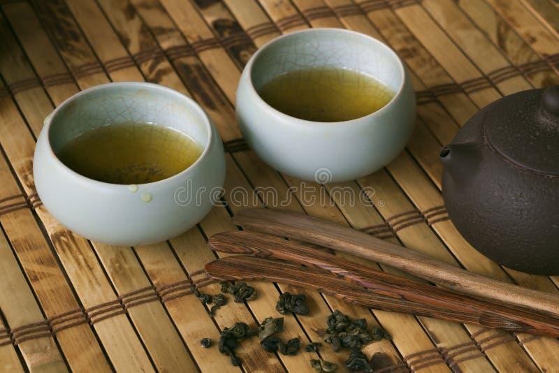 Pot et tasses de thé sur la table en bois image stock