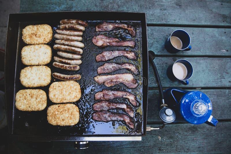 Pot frais de café avec le lard, la saucisse et les pommes de terre rissolées faisant cuire sur un gril chaud image stock
