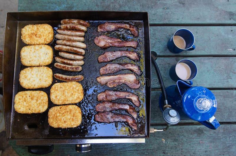 Pot frais de café avec le lard, la saucisse et les pommes de terre rissolées faisant cuire sur un gril chaud photos stock