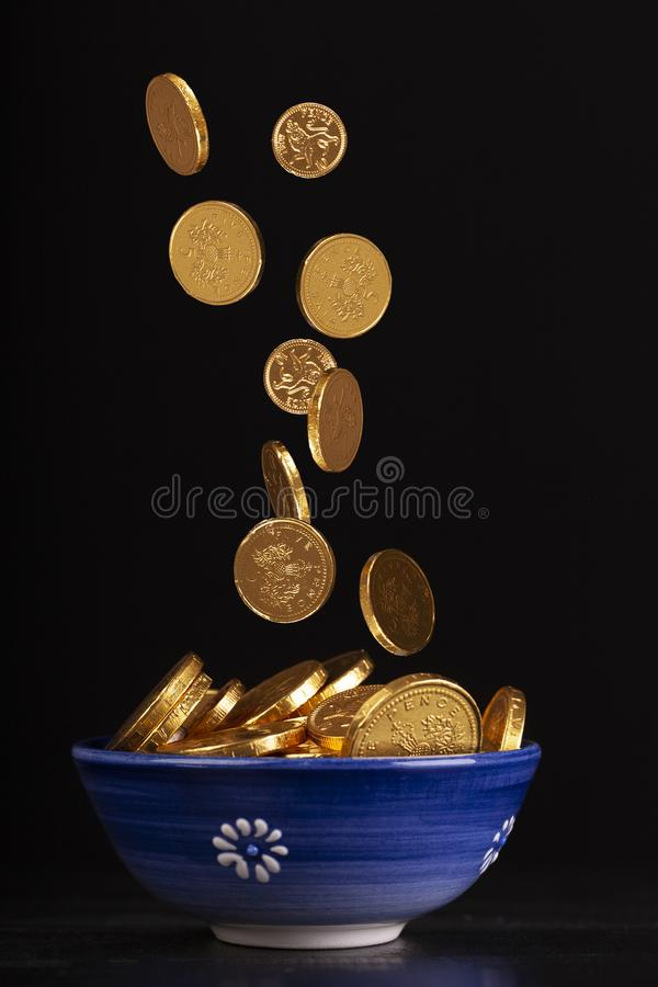 Pot of gold with blurred falling coins. Pot of gold concept with chocolate gold coins falling in to a pot on a black background royalty free stock photography