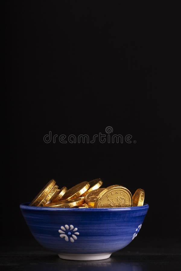 Pot of gold coins on black background. Pot of gold coins with black background. Blue dish with fake chocolate money. Rich wealth concept stock photos