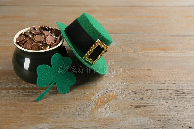Pot of gold coins, hat and felt clover leaf on table, space for text. St. Patrick`s Day celebration. Pot of gold coins, hat and felt clover leaf on wooden table royalty free stock images