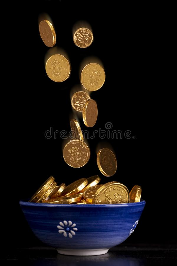 Pot of gold with falling coins. Pot of gold concept with chocolate gold coins falling in to a pot on a black background royalty free stock photography