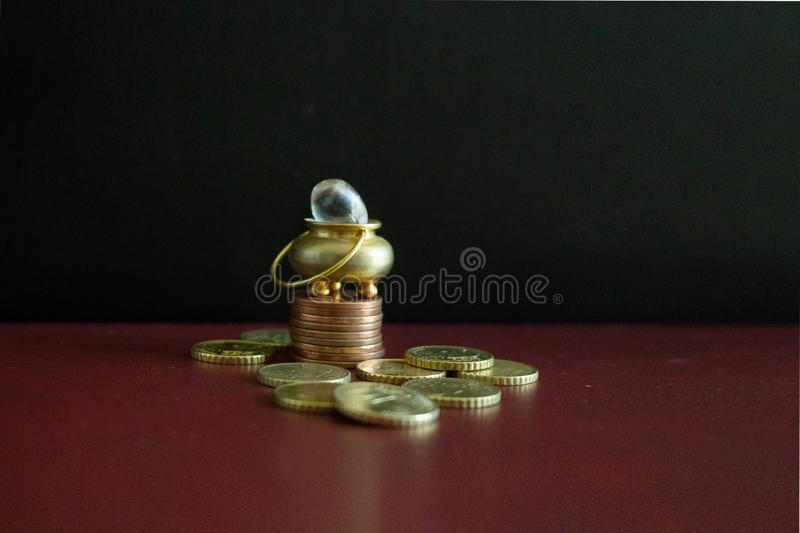 A pot of gold on top of some stacked coins royalty free stock image