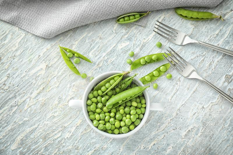 Pot with green peas on light background, top view stock image