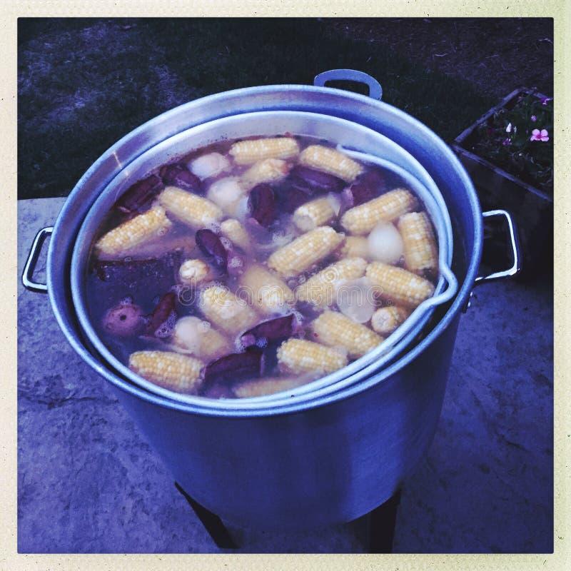 Pot of lowcountry seafood boil. Aluminum pot cooking lowcountry seafood boil with sweet corn, red potatoes, sausage, shrimp and crawfish stock image