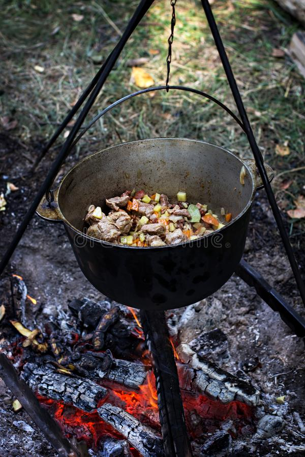 A pot of meat over a fire. Hike, summer vacation, outdoor recreation, outdoor food. Cooking over a campfire. tourist kettle over campfire royalty free stock image