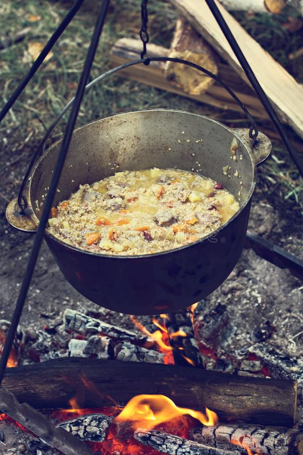 A pot of meat over a fire. Hike, summer vacation, outdoor recreation, outdoor food. Cooking over a campfire. tourist kettle over campfire stock photo