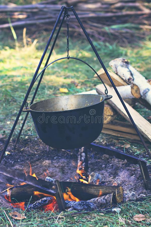 A pot of meat over a fire. Hike, summer vacation, outdoor recreation, outdoor food. Cooking over a campfire. tourist kettle over campfire stock image