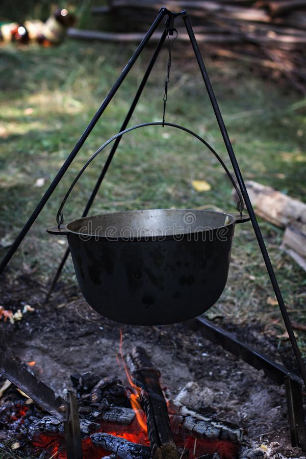 A pot of meat over a fire. Hike, summer vacation, outdoor recreation, outdoor food. Cooking over a campfire. tourist kettle over campfire royalty free stock images