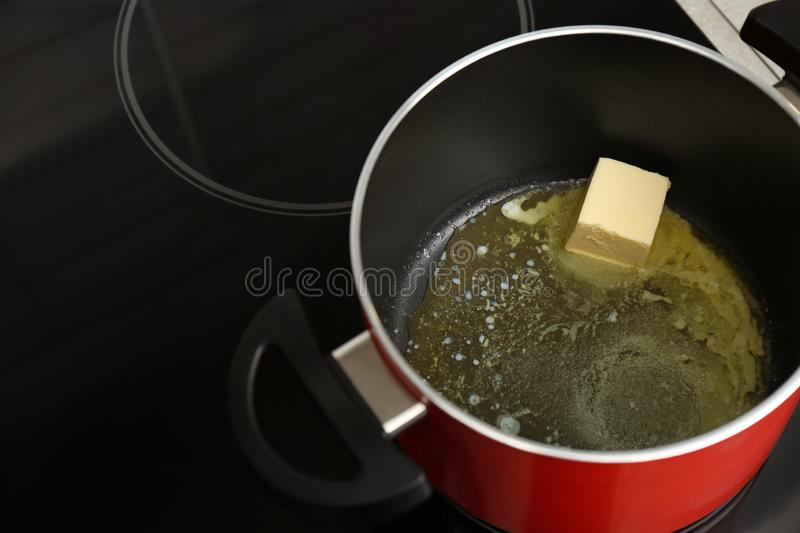 Pot with melted butter on stove royalty free stock photo