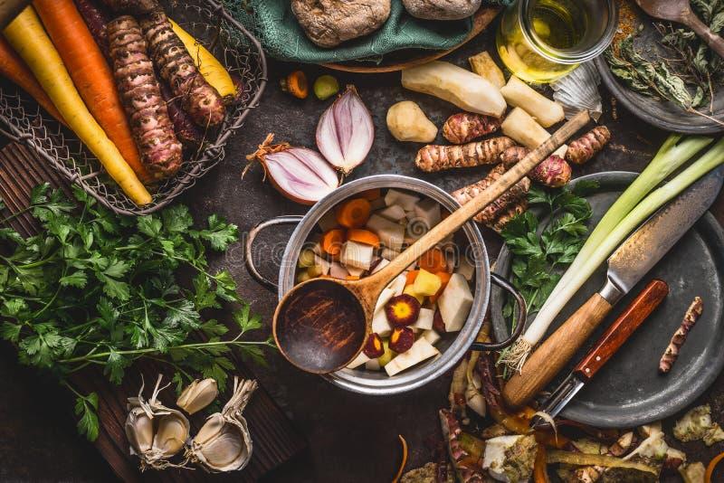 Pot met gesneden kleurrijke groenten en kokende lepel op donkere rustieke lijstachtergrond met organische vegetarische ingrediënt stock afbeeldingen