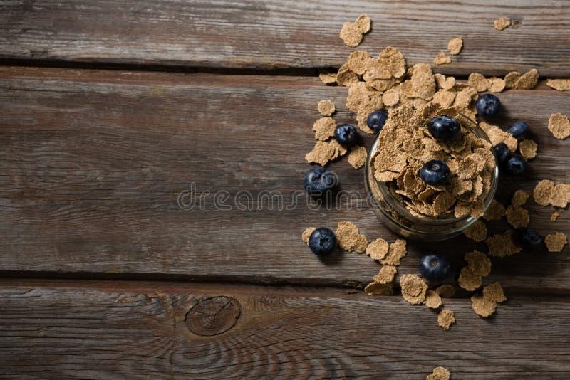 Pot rempli de flocons de blé et de baies bleues images libres de droits
