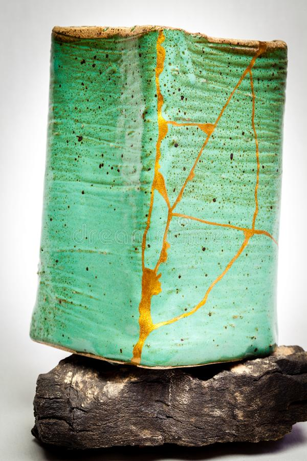 Pot repaired by kintsugi with gold royalty free stock images