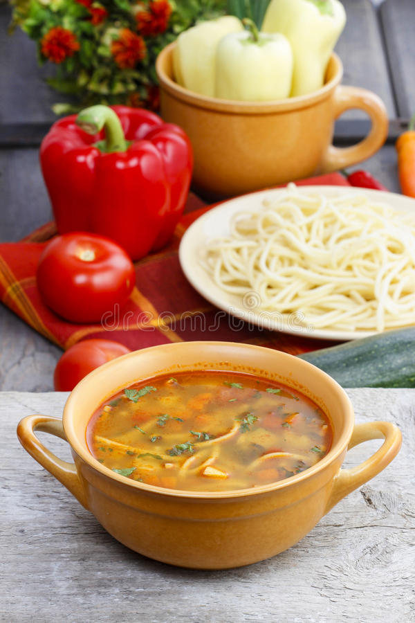 Pot of tomato soup and fresh vegetables. On old wooden table stock images