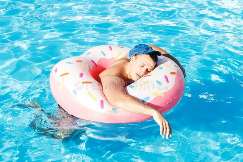 Potabile un turista russo su un nuoto gonfiabile della ciambella nello stagno immagini stock libere da diritti