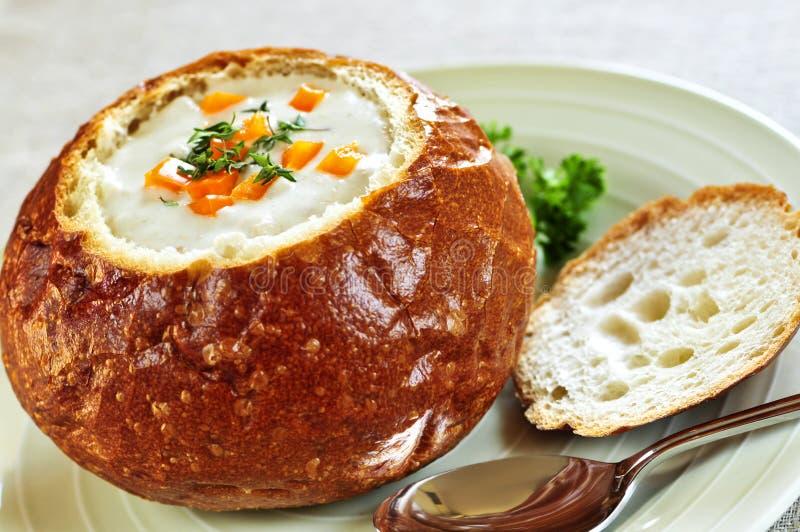 Potage dans le bol de pain image stock