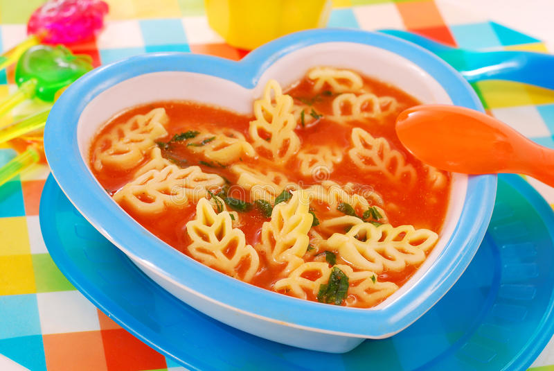 Potage de tomate avec des pâtes pour l'enfant photo stock