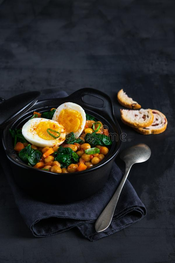 Potaje de Garbanzos chickpea stew Spanish recipe traditional with ingredients on a dark background with copy space. Vertical stock photo