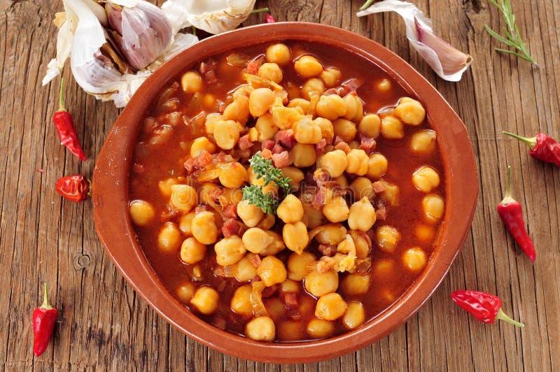 Potaje de garbanzos con jamon, spanish chickpeas stew with ham. An earthenware bowl with potaje de garbanzos con jamon, a spanish chickpeas stew with ham, on a stock photo