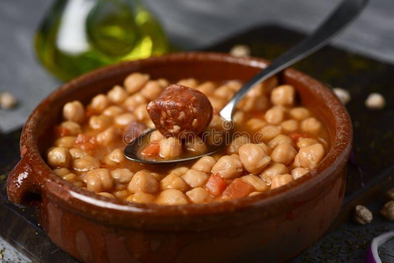 Potaje de garbanzos, spanish chickpeas stew. Closeup of an earthenware bowl with potaje de garbanzos, a spanish chickpeas stew with chorizo and serrano ham, on a stock images