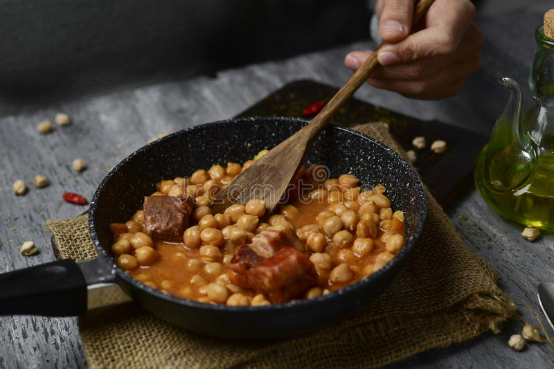 Potaje de garbanzos, spanish chickpeas stew. A frying pan with potaje de garbanzos, a spanish chickpeas stew with chorizo and serrano ham, on a rustic wooden royalty free stock image