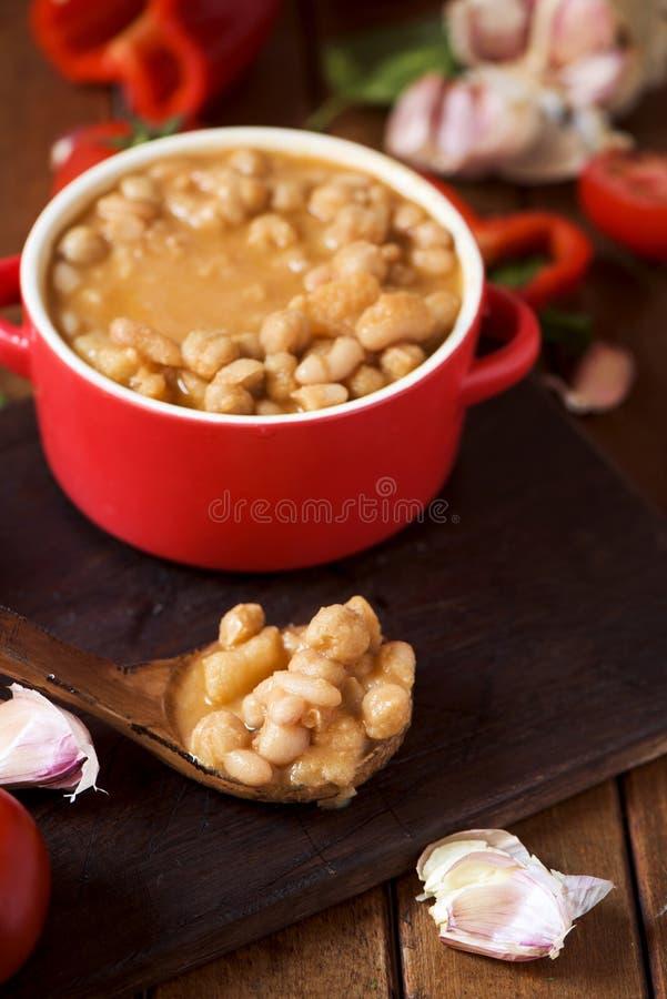 Potaje de garbanzos, a spanish chickpeas stew, on a wooden table. An earthenware casserole with potaje de garbanzos, a spanish chickpeas stew, and some stock photo
