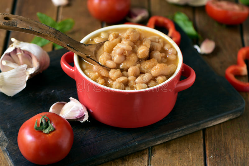 Potaje de garbanzos, a spanish chickpeas stew, on a wooden table. An earthenware casserole with potaje de garbanzos, a spanish chickpeas stew, and some stock images