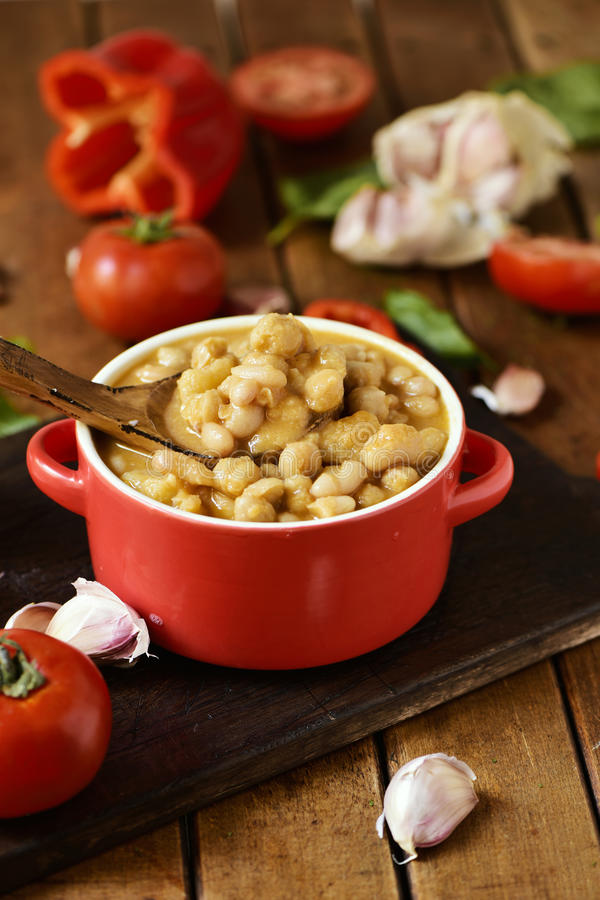 Potaje de garbanzos, a spanish chickpeas stew, on a wooden table. An earthenware casserole with potaje de garbanzos, a spanish chickpeas stew, and some royalty free stock images