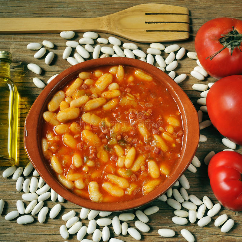 Potaje de judias, spanish white beans stew. An earthenware bowl with potaje de judias, a spanish white beans stew, on a rustic wooden table with the ingredients stock image