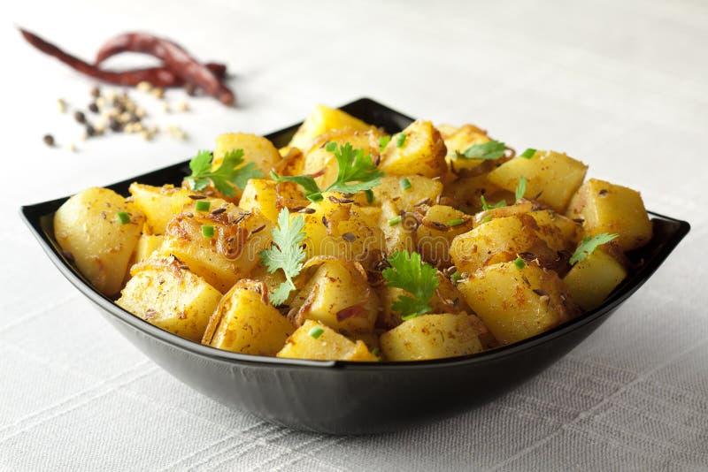 Potaoes frits épicés avec les graines de cumin rôties image libre de droits