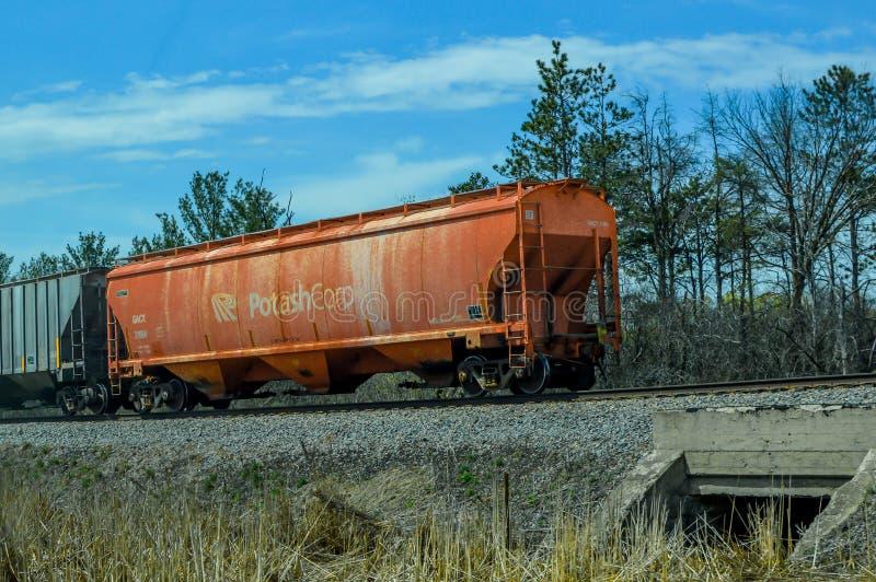 Potash Corp. Cargo Train Caboose on Railroad. An orange Potash Corp. Cargo Train Caboose traveling down the railroad tracks in Illinois stock photos