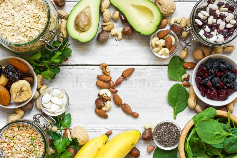 Potassium Food Sources as dried apricot, avocado, bean, chia seeds, banana, nuts, spinach. top view. flat lay stock image