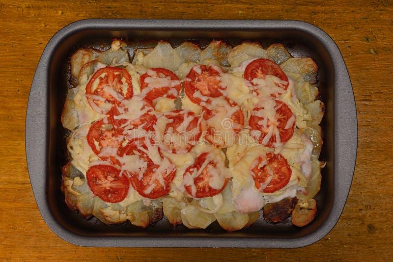Potatis bakad pudding med tomater och stycken av höna på en bakplåt På en träbordsskiva royaltyfri foto