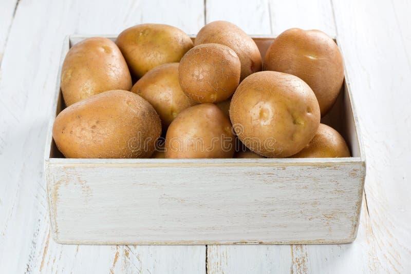 Potatis i en sjaskig träask royaltyfria bilder