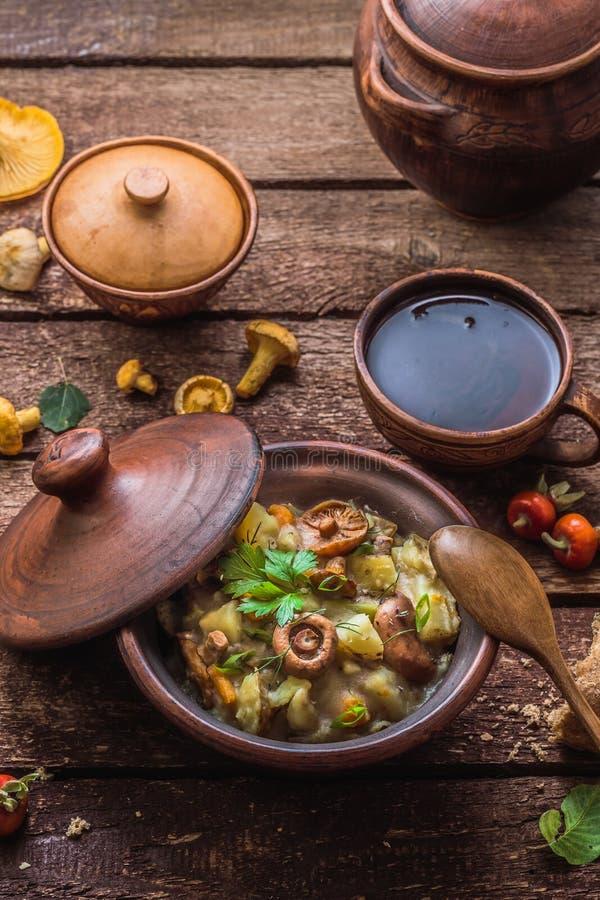 Potatis med champinjoner som låtas småkoka i en lerakruka, rysskokkonst, lantlig stil royaltyfria bilder