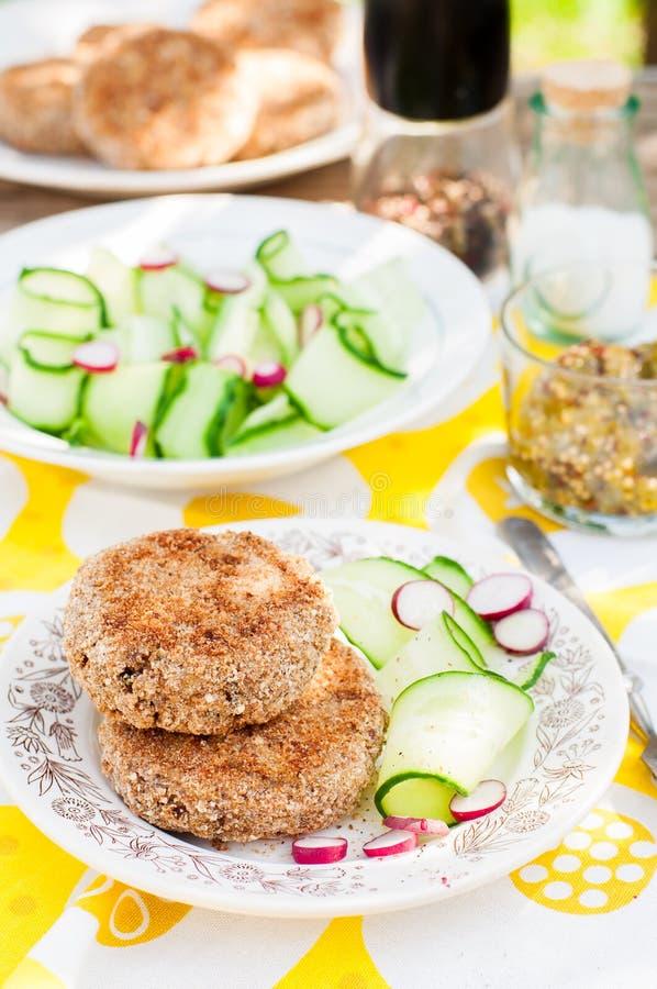 Potatis- och grisköttsmå pastejer med gurkan och Raddish sallad royaltyfria foton