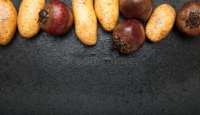 Potatis och röd beta på en svart bakgrund för tappning, tomt utrymme för text arkivfoton