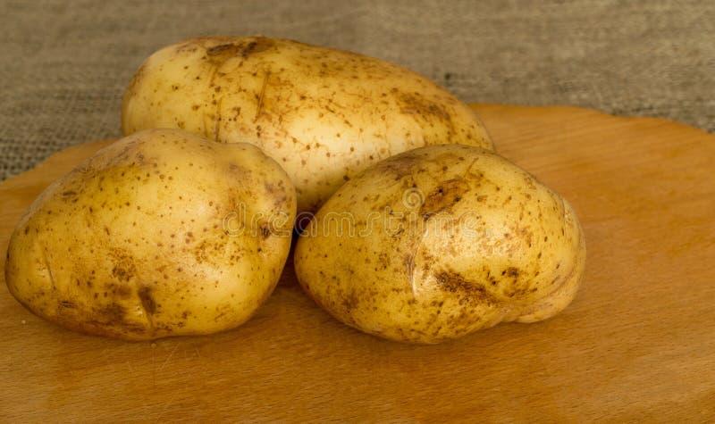 Potatis på träbräde royaltyfria foton