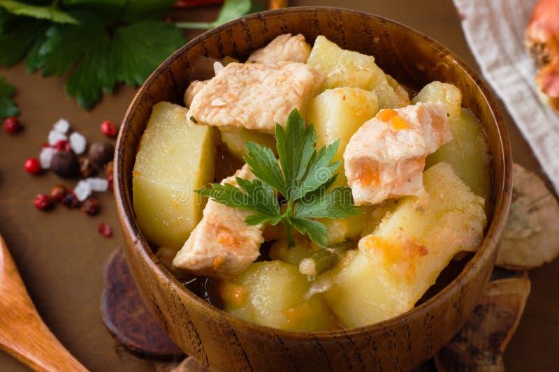 Potatisar lät småkoka med höna och grönsaker i en träbunke royaltyfri fotografi