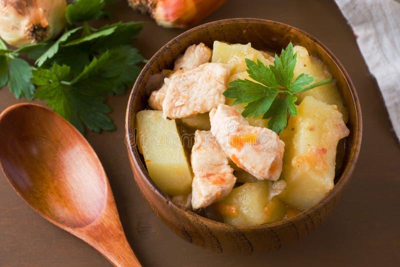 Potatisar lät småkoka med höna och grönsaker i en träbunke royaltyfri foto