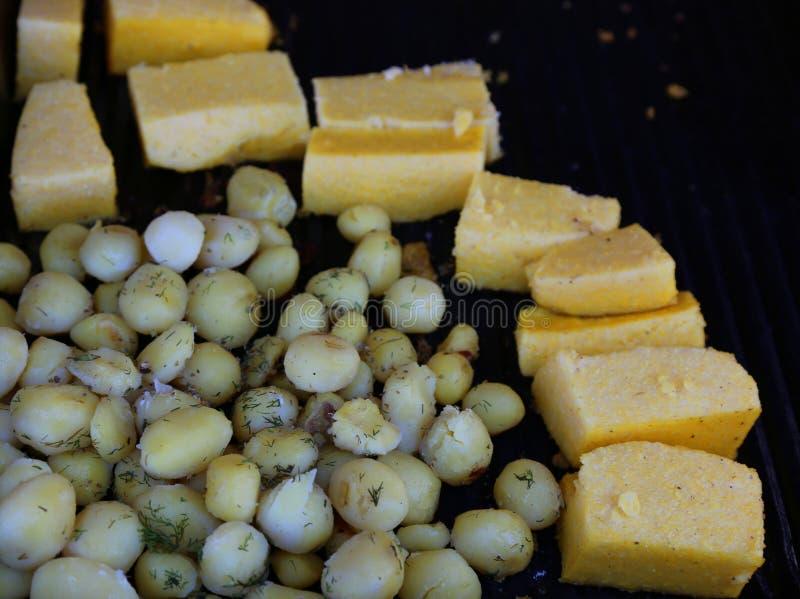 Potatisar med dill och stycken av polenta arkivfoton